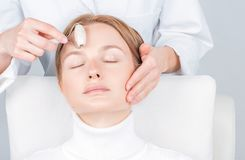 Beautiful woman having face treatment, cosmetologist massaging forehead with jade rollers royalty free stock photo