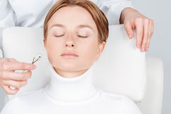 Beautiful woman having face treatment, cosmetologist massaging face with jade rollers royalty free stock image