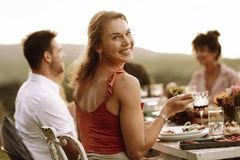 Beautiful woman having food with friends at party stock images