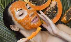 Beautiful woman having fresh papaya facial mask apply. fresh pap Stock Photos