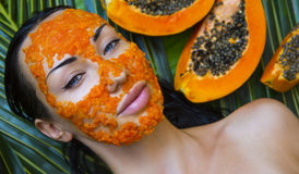 Beautiful woman having fresh papaya facial mask apply. fresh pap Royalty Free Stock Image