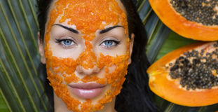 Beautiful woman having fresh papaya facial mask apply. fresh pap Royalty Free Stock Photo