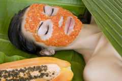 Beautiful woman having fresh papaya facial mask apply. fresh pap Royalty Free Stock Photo