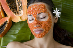 Beautiful woman having fresh papaya facial mask apply. fresh pap Royalty Free Stock Images