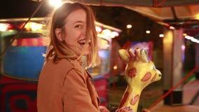 Beautiful woman having fun riding carousel in amusement park stock video