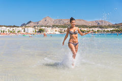 Beautiful woman having fun at seaside in Mallorca. Tanned young woman wearing bikini, running and splashing water all around. Summer and happiness concepts Stock Photos