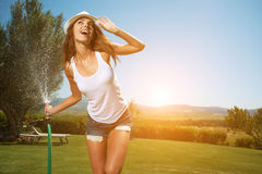 Beautiful woman having fun in summer garden with garden ho Stock Photography