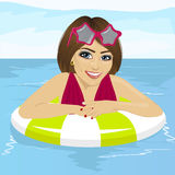 Beautiful woman having fun at swimming pool with inflatable ring Stock Photos