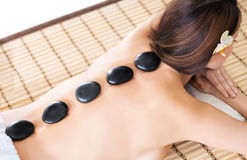 Beautiful woman having hot stones on her back in spa salon Stock Photos