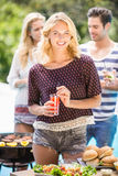 Beautiful woman having juice at outdoors barbecue party Royalty Free Stock Image