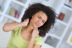 Beautiful woman having pain in neck. Beautiful woman is having pain in her neck Stock Photo