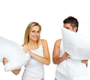 Beautiful woman having a pillow fight with a man. In bed royalty free stock photo