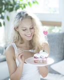 Beautiful woman having raspberry cake with fork in house Stock Photography