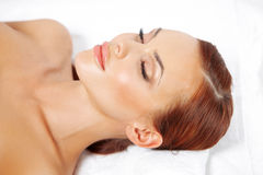 Beautiful woman having a spa treatment. Beautiful woman lying back and relaxing with her eyes closed as she enjoys the luxury of having a spa treatment Royalty Free Stock Photos