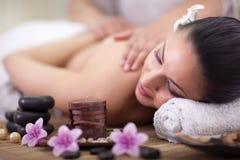 Beautiful woman having a wellness back massage at spa salon royalty free stock photography