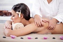 Beautiful woman having a wellness back massage at spa salon Stock Photos