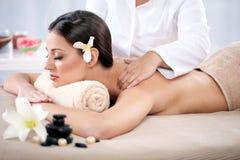 Beautiful woman having a wellness back massage at spa salon Stock Image