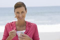 Beautiful Woman Having Yoghurt On Beach Royalty Free Stock Photos
