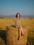 Beautiful woman on hay stack hands wind Stock Image
