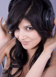 Beautiful woman with headphones. Portrait of a beautiful young woman listening on headphones, sitting royalty free stock photos