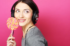 Beautiful woman with headphones and candy Royalty Free Stock Photography