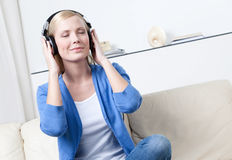 Beautiful woman in headphones listens to music Stock Images