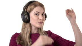 Beautiful woman with headphones listens to music and making silly gestures. Crazy dancing. Isolated. Beautiful woman in pink dress with headphones listens to stock footage