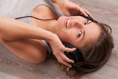 Beautiful woman with headphones lying on the floor Stock Images