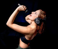 Beautiful  woman with headphones and mic singing Stock Photos