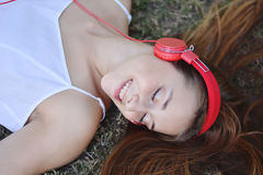 Beautiful woman with headphones outdoors. Royalty Free Stock Image