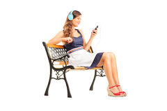 Beautiful woman with headphones sitting on bench Stock Images