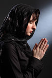 Beautiful woman in headscarf praying eyes closed. Beautiful young woman wearing black headscarf, eyes closed and hands together in prayer Royalty Free Stock Photo
