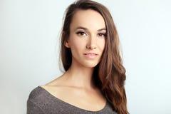Beautiful woman headshot. Near the wall, light grey background Stock Photography