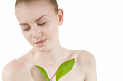 Beautiful woman with a healthy complexion. Beautiful woman with a healthy and well-groomed complexion holding green leaf . Spy beauty skin treatment woman royalty free stock photo