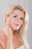Beautiful woman with a healthy skin. Touching her face Stock Photo
