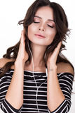Beautiful woman with healthy skin, hair curls and headphones, posing in studio. Beauty face. Royalty Free Stock Image
