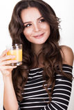 Beautiful woman with healthy skin, hair curls and orange juice, posing in studio. Beauty face. Royalty Free Stock Photo