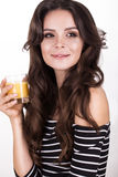 Beautiful woman with healthy skin, hair curls and orange juice, posing in studio. Beauty face. Royalty Free Stock Images