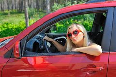 Beautiful woman in heart shaped glasses in car Royalty Free Stock Image