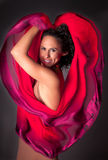 Beautiful Woman Hearted by her red scarf. Gorgeous red Valentine's Day heart surrounds a Beautiful woman Royalty Free Stock Photography