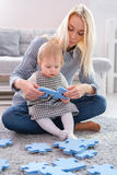 Beautiful woman and her baby playing with puzzle pieces while sitting on a carpet in the living room Royalty Free Stock Images