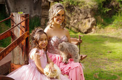 Beautiful woman and her cute little daughter looking at camera and smiling, wearing a princess dress, while they are Stock Photos