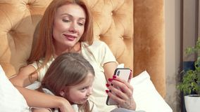 Beautiful woman and her cute little daughter using smart phone at home together. Adorable little girl enjoying watching something online with her mom. Internet stock video