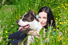 Beautiful woman with her dog. Sitting in the grass Stock Image