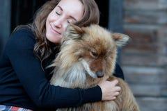 A beautiful woman and her dog nenets shepherd laika sitting. A beautiful woman and her dog nenets shepherd laika sitting near house. Friendship between man and stock photo