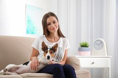 Beautiful woman with her dog sitting on sofa. At home royalty free stock photography