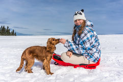 Beautiful woman with her dog on the snow Stock Photo