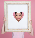 Beautiful woman with her face framed by a heart Stock Photo