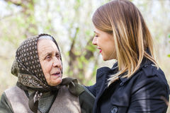 Beautiful woman with her grandmother outdoor. Picture of a beautiful women spending time with her sick grandmother outdoor Royalty Free Stock Image