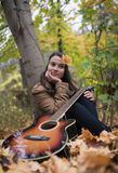 Beautiful woman with her guitar. An melancholic girl with her guitar in autumn season stock photo